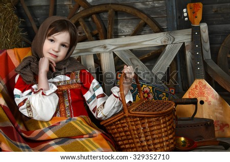 Beautiful girl in russian costume sitting in a traditional interior - stock photo