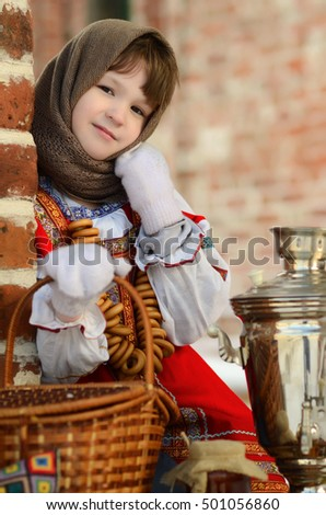 Beautiful girl in russian costume sitting in a traditional location