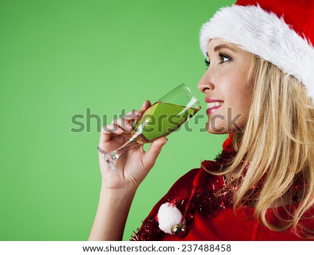 Beautiful girl in Santa Claus hat with champagne glass - stock photo