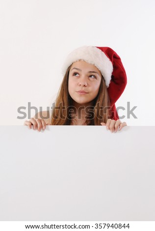beautiful girl in Santa hat holding white board and dreaming about Christmas gift, Christmas holiday, happy holiday concept - stock photo