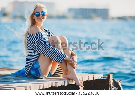 Beautiful Girl in sea style sitting on wooden bridge. Travel and Vacation. Freedom Concept. Sensual blonde beautiful woman, Girl with perfect body and long healthy hair,Marine style - stock photo