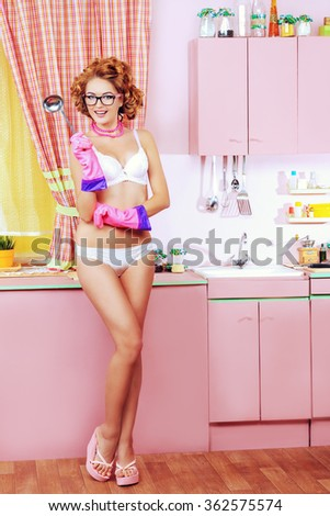 Beautiful girl in sexy lingerie alluring on her glamorous pink kitchen. Fashion. Full length portrait.