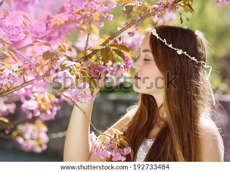 Beautiful girl in spring garden among the blooming trees with pink flowers - stock photo