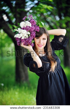 beautiful girl in spring with a bouquet of lilacs. - stock photo