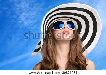 beautiful girl in striped hat and sunglasses on background blue sky - stock photo