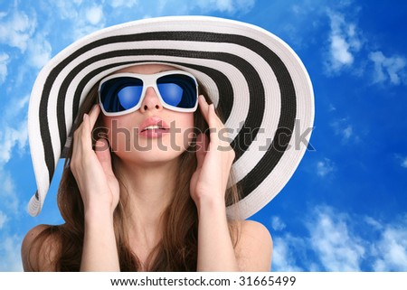 beautiful girl in striped hat and sunglasses with hands near face on background of the blue sky - stock photo