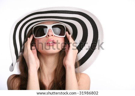 beautiful girl in striped hat and sunglasses with hands near face on the white background - stock photo
