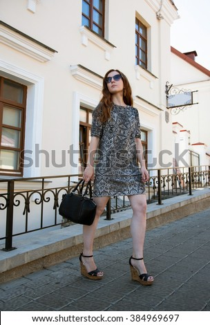 Beautiful girl in sun glasses walking on the town street