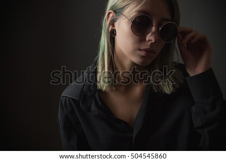 Beautiful girl in sunglasses on a black background. Studio portrait