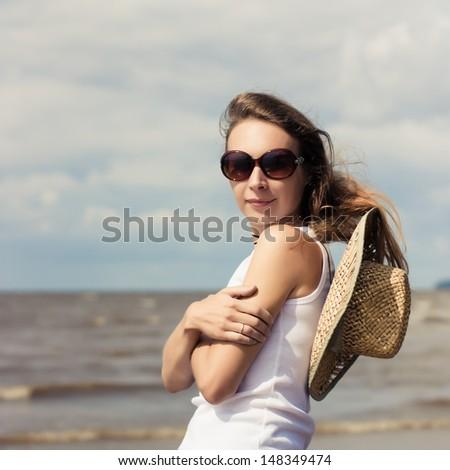 Beautiful girl in sunglasses on the sunny beach. - stock photo
