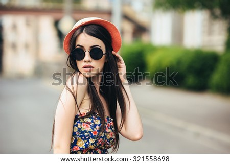 beautiful girl in sunglasses posing for the camera in the city - stock photo