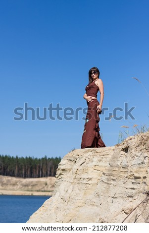 beautiful girl in sunglasses standing near the lake in sunny day on blue sky background