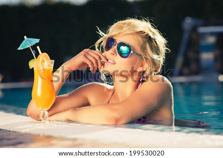 beautiful girl in sunglasses with fresh orange juice in luxury pool. Vogue style - stock photo