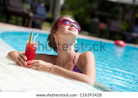 beautiful girl in sunglasses with fresh watermelon juice in luxury pool - stock photo