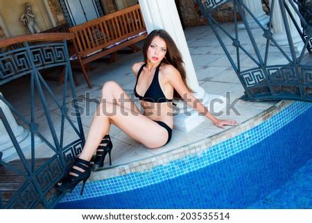 Beautiful girl in swimsuit sitting on the floor - stock photo