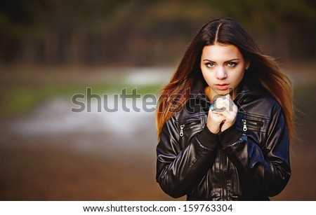 Beautiful girl in the autumn forest trying to keep warm