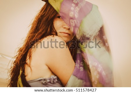 Beautiful girl in the beach wearing in colored piece of fabric on the wind. Old lens style