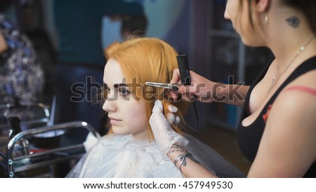 Beautiful girl in the client's chair beauty salon. Master prepares hairstyle model for painting, special attaches clothespins to the hair.
