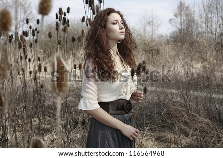 Beautiful girl in the fall nature with long dark curly hair - stock photo