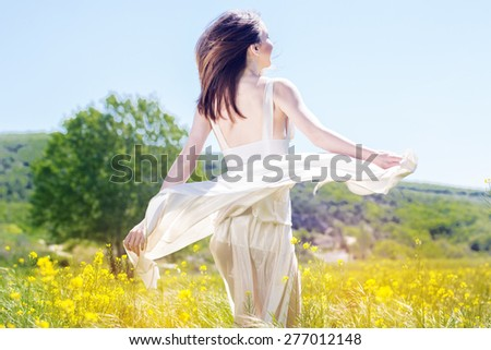 Beautiful girl in the field of yellow flowers is wearing flying white wedding dress - stock photo