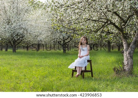 Beautiful girl in the flowered apple orchard