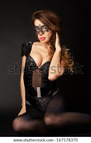 Beautiful girl in the masquerade mask on a black background. Portrait of sexy woman with black party mask on face.