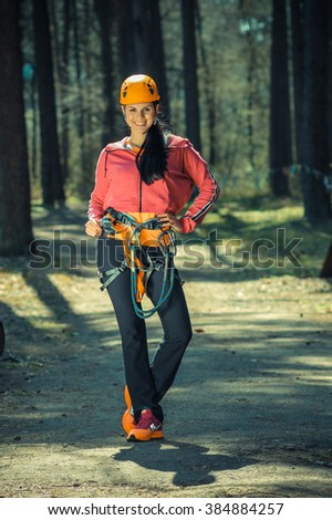 Beautiful girl in the outfit climbing climbs over obstacles between trees