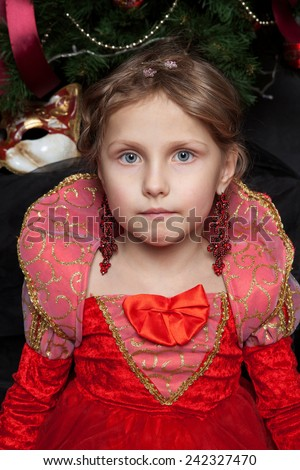 Beautiful girl in the photo studio on textured background in a red dress and red long earrings in the form of a princess - stock photo