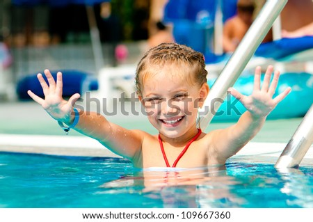 beautiful girl in the pool lifted hands up - stock photo