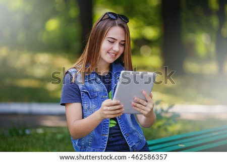 Beautiful girl in the summer park using tablet.