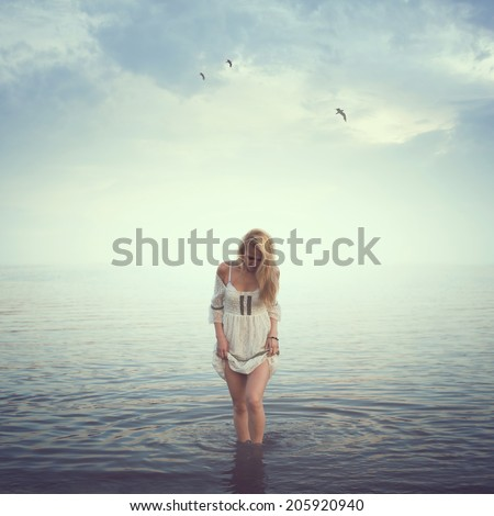 Beautiful girl in the water. Beach, sunrise, cold morning. concept loneliness love sadness romance - stock photo