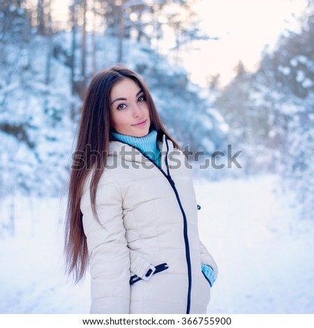 beautiful girl in the winter. the girl against snow branches. the girl rejoices to winter weather. the girl in the beautiful winter wood. the girl with a beautiful smile in the winter wood.