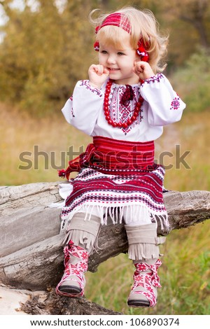 Beautiful girl in ukrainian costume sitting on a log outdoor - stock photo
