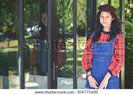 Beautiful Girl in vintage style. Reflection of woman on the door glass at coffee shop - stock photo