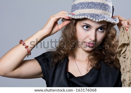 Beautiful girl in warm hat looks into aside. Isolated on gray background