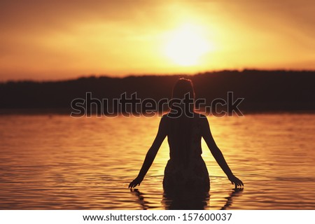 beautiful girl in water on sunset silhouette