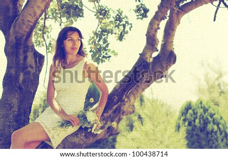 Beautiful girl in white dress sitting on the tree - stock photo