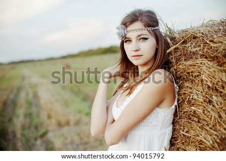 beautiful girl in white dress standing behind haystacks - stock photo