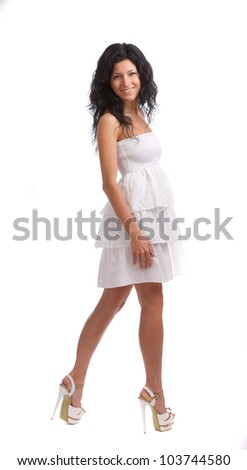 Beautiful girl in white dress standing on white background.