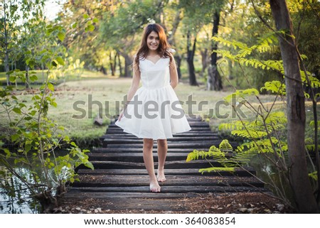 Beautiful girl in white dress walking barefoot on the small wooden brideg over the ditch in the park - stock photo