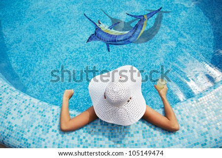 beautiful girl in white hat relaxing near a swimming pool - stock photo