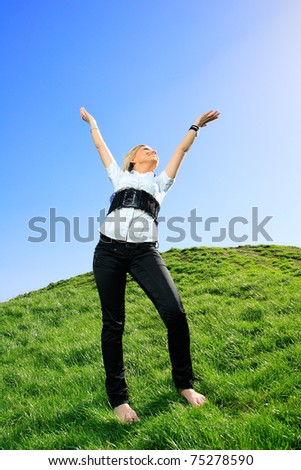 beautiful girl in white shirts and jeans on the hill arms up in the air