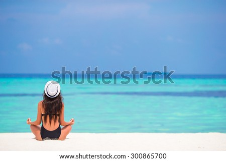 Beautiful girl in yoga position during tropical vacation - stock photo