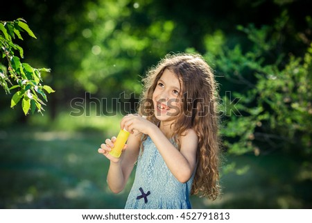 Beautiful girl is blowing a bubbles in park