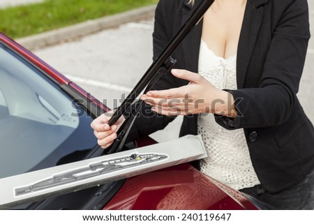 Beautiful girl is changing windscreen wipers on a car
