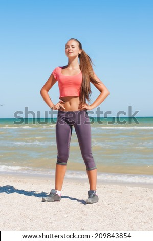 Beautiful girl is engaged in yoga on the beach in summer - stock photo
