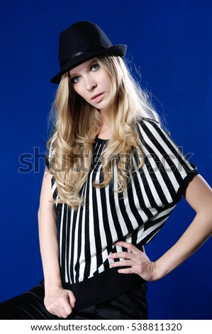 beautiful girl is in fashion style,in,hat sitting on blue background
