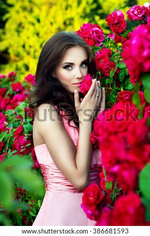 Beautiful girl is in roses in nature