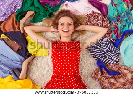 Beautiful girl is looking at camera and smiling, lying among high heeled shoes and fashionable clothes on the floor in a dressing room - stock photo