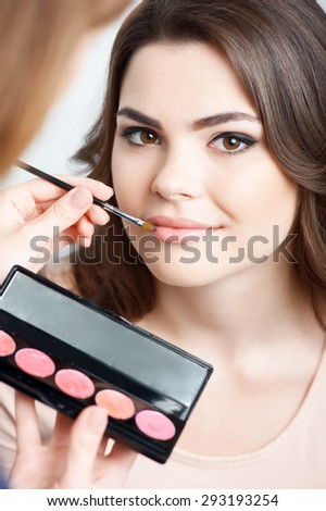 Beautiful girl is looking at the camera. Another lady makes-up her. She is touching brush to her lips and holding set of pomade. Isolated on grey background
